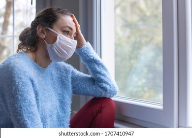 Young woman wearing a face mask and peeking out from window. Woman in quarantine looking through the window. Corona covid-19 virus protection.