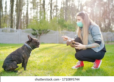 Young Woman Wearing Face Mask Play With Cute Dog in Home Garden or Park. Coronavirus Pandemic New Normal.