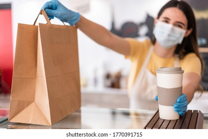 Young woman wearing face mask while serving takeaway breakfast and coffee inside cafeteria restaurant - Worker preparing delivery food inside bakery bar during coronavirus period - Focus on right hand