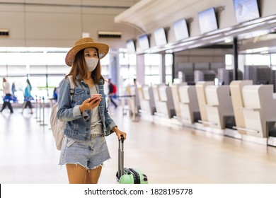 Young woman wearing a face mask and holding a mobile phone is looking for a check-in counter at the airport, New normal lifestyle concept