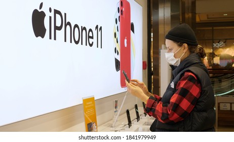 Young Woman Wearing Face Mask Choosing Smartphone In Apple Store During Coronavirus Outbreak. Warsaw, Poland, 27 Oct, 2020.
