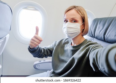 Young woman wearing face mask is traveling on airplane. New normal travel covid-19 pandemic concept.