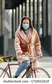 Joven con mascarilla médica mientras monta una bicicleta durante la cuarentena al aire libre