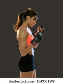 Young woman wearing fighting gloves isolated on a gray background