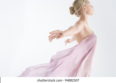 Young woman wearing a floating sarong with arms outstretched back.