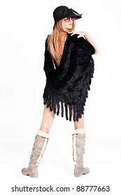 young woman wearing fur and winter boots, full body shot, studio shot