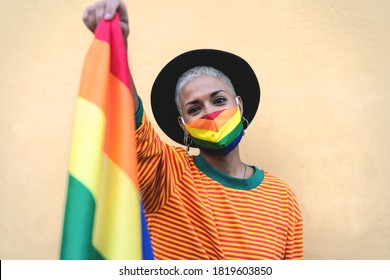 Young woman wearing gay pride mask holding rainbow flag symbol of Lgbtq social movement