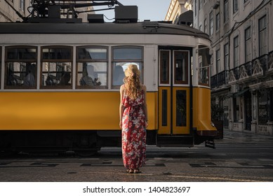 Young woman wearing generic red sundress walking on the Lisbon city street and looking at passing typical yellow tram with tourists
