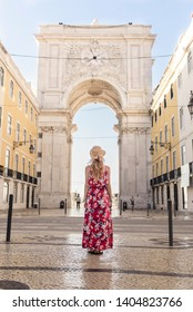 Young woman wearing generic sundress walking through the Lisbon old town and looking at Augusta Arch, built in 1873
