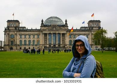 Young woman wearing glasses with backpack in front of the Bundestag building in Berlin. Erasmus student, studying abroad and tourist concept.
