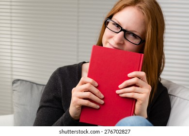 A young woman wearing glasses holds a red book in her hands and smiles at the camera.