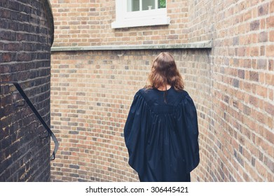 A young woman wearing a graduation gown is walking down some stairs outside by a brick wall