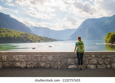 Young woman wearing green backpack is standing on the bridge near Bohinj lake looking at the view in Bohinj, Slovenia