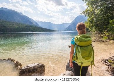 Young woman wearing green backpack is standing by the Bohinj lake in Bohinj, Slovenia