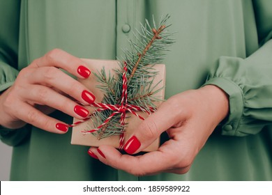 Young woman wearing green dress holding Christmas present box decorated with Christmas tree twig. Christmas holidays and New Year celebration concept. Preparing family gifts for Christmas