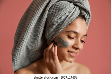 Young woman wearing grey towel applying clay mask on her face, while standing at the studio. Adorable woman with towel on hair and clay mask on face. Beauty concept