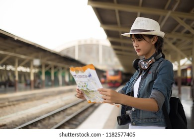 Young woman wearing hat with backpack looking of the mass rapid transit route map  in train station for check next station for travel,travel concept,backpack,blurred background