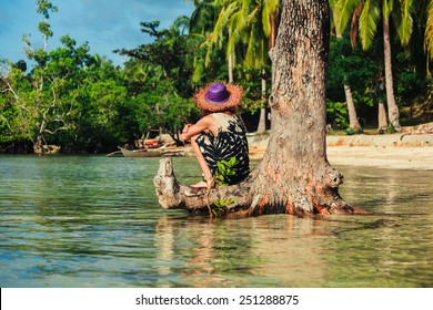 A young woman wearing a hat by a tree on a tropical beach