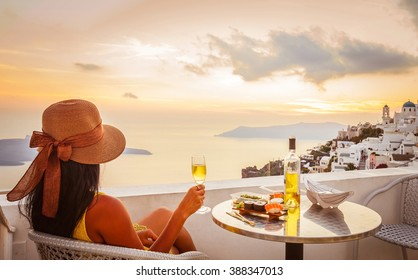 Young woman wearing hat, looking at beautiful view of Caldera and enjoying romantic dinner during sunset before getting dark over Aegean sea, Santorini