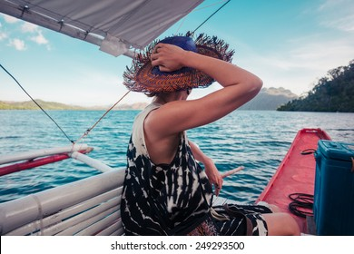 A young woman wearing a hat is on a boat in the tropics