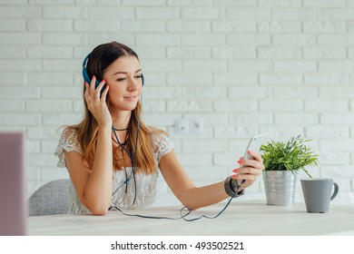 Young woman is wearing headphones and using smartphone
