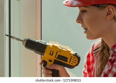 Young woman wearing helmet using power drill and tools for work at home, installing windows. Girl working at flat remodeling. Building, repair and renovation.