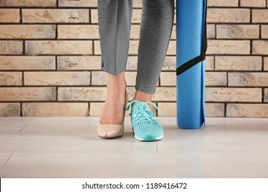 Young woman wearing high-heeled shoe and sneaker near brick wall. Concept of balance between rest and work