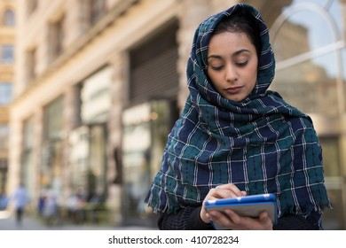 Young woman wearing hijab head scarf in city using tablet pc computer