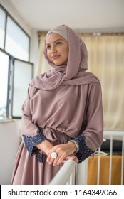 young woman wearing hijab standing in hallway