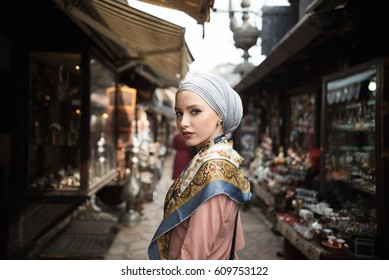 young woman wearing hijab walking on street
