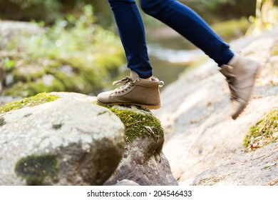 young woman wearing hiking boots mountain climbing