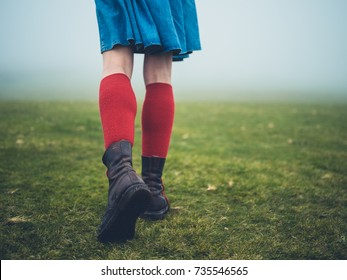 A young  woman wearing hiking boots and socks is walking on the moor in the fog