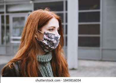 young woman wearing homemade everyday cloth face mask outdoors in city, new normal covid-19 corona virus pandemic or air pollution concept, real people lifestyle in winter