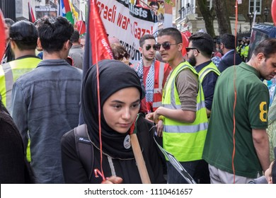 A young woman wearing an Islamic head scarf walks through the crowds during the Al Quds Day rally, London, 10/06/18.