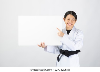 Young woman wearing Karate suite holding a white board with happy face