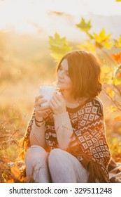 Young woman wearing knitted poncho having picnic in a forest: drinking tea and picking apples. Fall concept