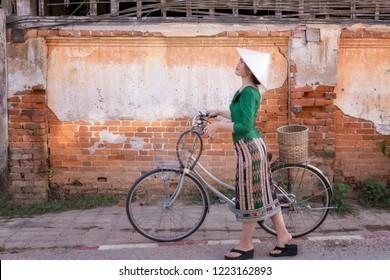 Young woman wearing Laos traditional dress with bicycle walking tourism in walking street Chiang Khan Loei Thailand.