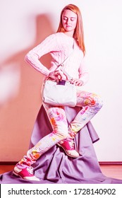 Young woman wearing light pink knit sweater, light colorful pants, red and white leather sneakers, shoulder carrying light gray leather, fingers picking out cell phone from bag. Color filtered effect