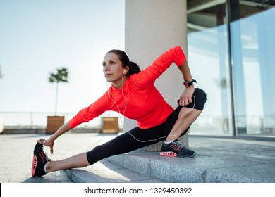 Young woman wearing long sleeve t-shirt listening music while stretching before jogging exercise