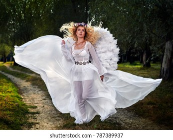 young woman wearing long white dress and angel wings