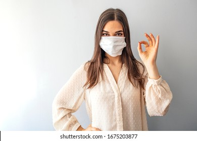 Young woman wearing medical face mask, studio portrait. Woman Wearing Protective Mask and Showing OK sign. Woman wearing surgical mask for corona virus