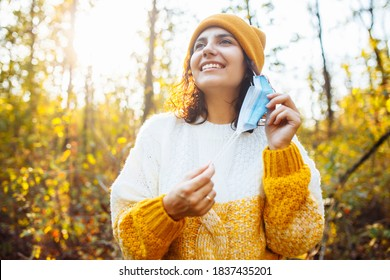 Young woman wearing an orange hat and sweater takes off the medical sterile mask in the autumn forest. Female breathes fresh air in fall park during coronavirus covid-19 pandemic. Healthcare concept.