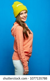 Young woman wearing pink hoodie with yellow hat. Portrait of casual dressed girl sanding sideways on blue background.