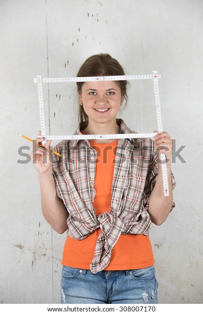 Young woman wearing  plaid shirt holding a ruler in the form of a square frame in the front of wall, smiling