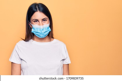 Young woman wearing protection mask for coronavirus disease over yellow background with a happy and cool smile on face. Lucky person.