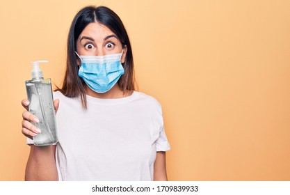 Young woman wearing protection mask for coronavirus holding hand sanitazer against virus disease scared and amazed with open mouth for surprise, disbelief face