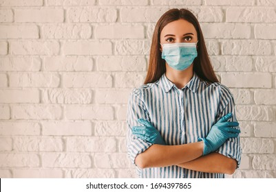 Young woman wearing protective mask on face and medical gloves keeping arms crossed in hospital. Confident girl, female doctor in medical mask and protective gloves. Coronavirus COVID-19 protection