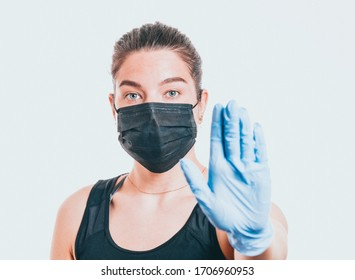 Young woman wearing protective mask on face and medical gloves. Showing stop sign. Confident girl, female doctor in medical mask and protective gloves. Coronavirus COVID-19 protection.