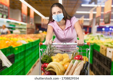 Young woman wearing a protective mask with shopping cart at the supermarket