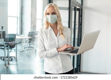 Young woman wearing protective mask on her face during coronavirus epidemic at work. Office photography, working at a computer, making notes.